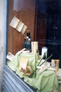 Window display in Marseilles showing Notre Dame de la Confession, green candles, and boat-shaped cookies called navettes